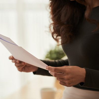 Cropped image of business woman reading documents in her hands